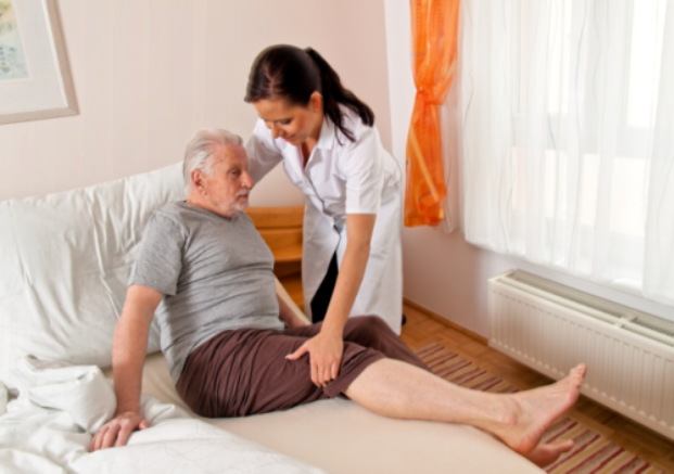 caregiver helping patient in getting up to bed